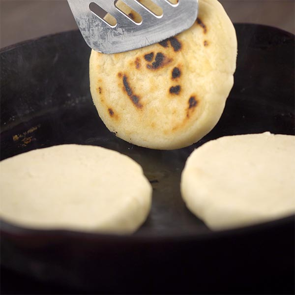 Flipping arepas on the skillet