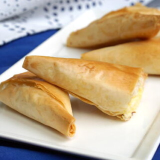 Light and flaky Greek pies pies filled with feta cheese, Tiropita make for a wonderful appetizer or snack that everyone is sure to enjoy! | www.CuriousCuisiniere.com