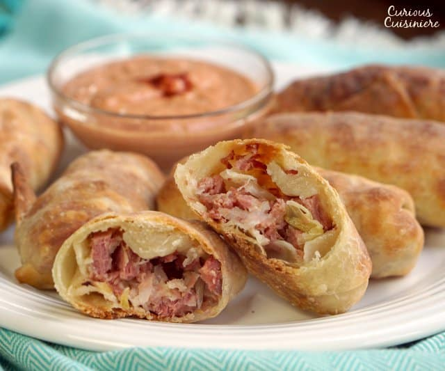 All the flavor of a Reuben sandwich in a little hand-held appetizer, these Baked Reuben Egg Rolls are the perfect recipe for a St. Patrick's Day party or any party! | www.CuriousCuisiniere.com