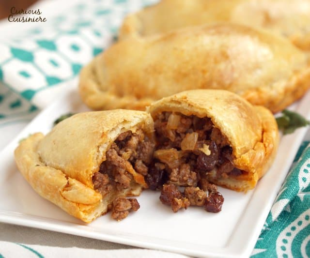 Chilean Empanadas de Pino are flavorful beef empanadas filled with unexpected ingredients like raisins, olives, and hard boiled eggs. These make a great meal on the go and are perfect for a make-ahead meal! | www.CuriousCuisiniere.com
