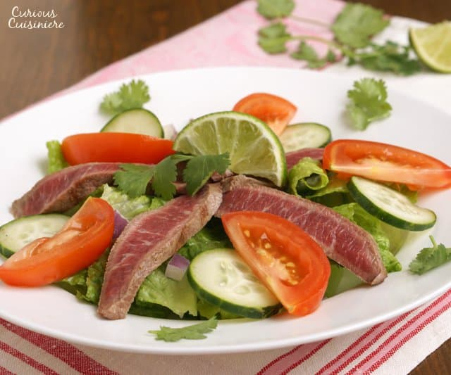 This grilled Thai Beef Salad, Yam Neua, is a simple salad with a bright and tangy Thai dressing, making for an easy and lighter way to enjoy your leftover summer grilled steak. | www.CuriousCuisiniere.com