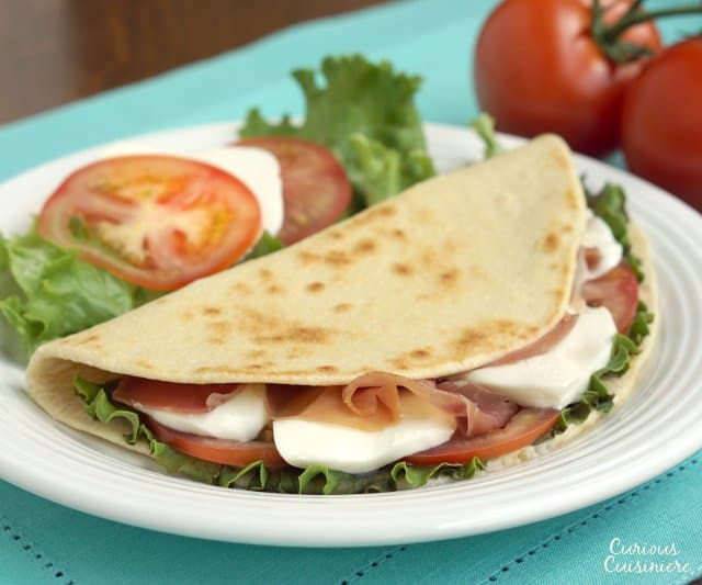 Piadina are thin, Italian flatbreads that are made by street vendors and sold sandwich-style loaded with tasty fillings like fresh mozzarella and flavorful prosciutto.  | www.CuriousCuisiniere.com