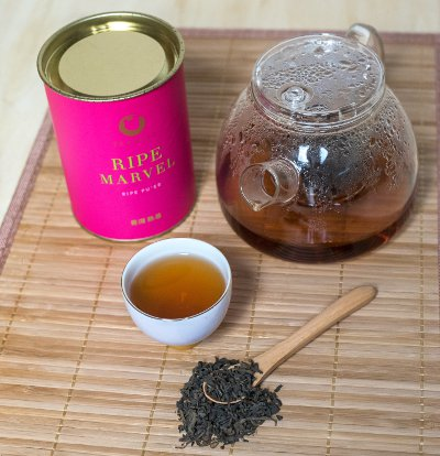 Pink tea canister with glass tea pot and loose tea.