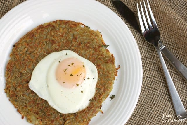SSwiss Potato Rosti is your classic recipe for a satisfying potato pancake. Traditionally eaten for breakfast, we serve our Rosti with eggs. It's the perfect way to start the day! | www.CuriousCuisiniere.com