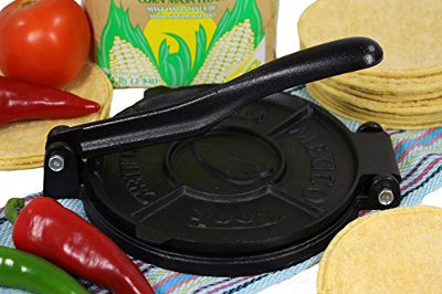 Black iron tortilla press surrounded by ingredients.