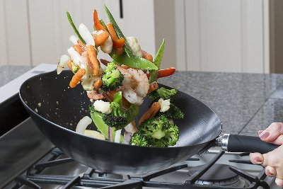 Wok with tossing vegetables and shrimp.