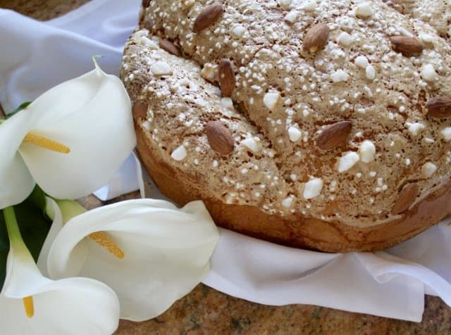 "Colomba di Pasqua (literally ""Easter dove"") is a panettone-like bread that is shaped in the form of a dove. Almond studded bread with Easter lilies."