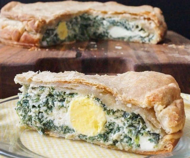Torta Pasqualina is a savory Italian pie filled with greens and ricotta cheese that is traditionally enjoyed for Easter. Image of cut pie with greens and hard cooked egg showing in the slice.
