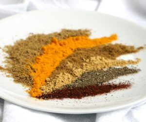 Warm ground spices arranged on a white plate. High angle.
