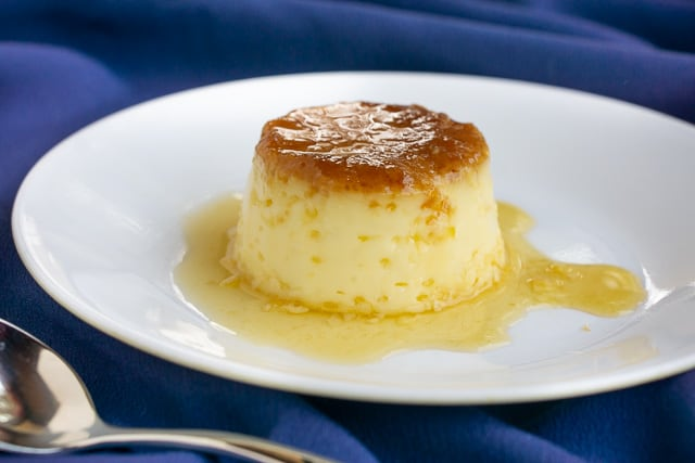 Individual serving of Spanish flan on a plate surrounded by caramel.  | www.CuriousCuisiniere.com