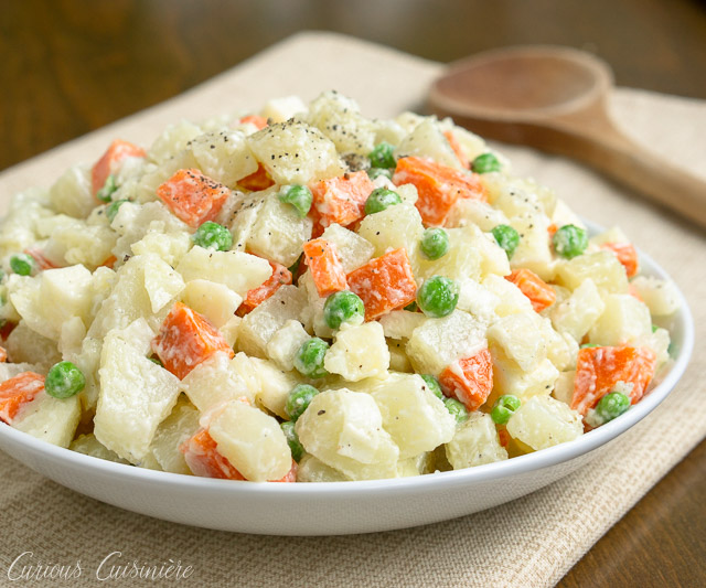 Ensalada Rusa is the Spanish name for a side dish that is popular in many countries but is best known as Oliver Salad, or Russian Potato Salad. This well known potato salad is full of vegetables, like peas, carrots, onions, and more. | www.CuriousCuisiniere.com