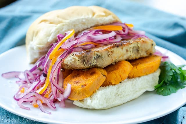 Pan Con Chicharron is a flavorful Peruvian sandwich made from the unique combination of slow braised pork and sweet potato topped with a crisp red onion relish. In Peru, it's traditionally eaten for breakfast, but we think it's the perfect meal for any time of day! | www.CuriousCuisiniere.com