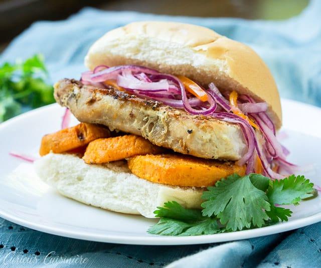 Sandwich de Chicharron is a Peruvian Pork Sandwich with a unique combination of braised pork, sweet potato and salsa criolla. | www.CuriousCuisiniere.com