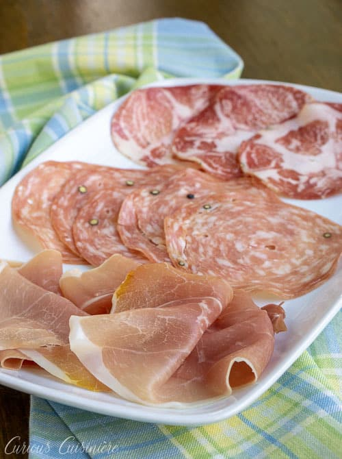 Have you heard of salumi? These tasty Italian cured meats, including Prosciutto, Pancetta, and Capocollo are perfect for sandwiches, appetizer spreads, and so much more!  | www.CuriousCuisiniere.com