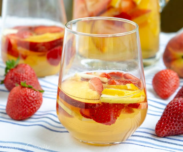This Strawberry Peach Sangria is a fun twist on Spanish White Sangria. Fresh fruit, a crisp white wine, and a splash of brandy make this a summer favorite! | www.CuriousCuisiniere.com