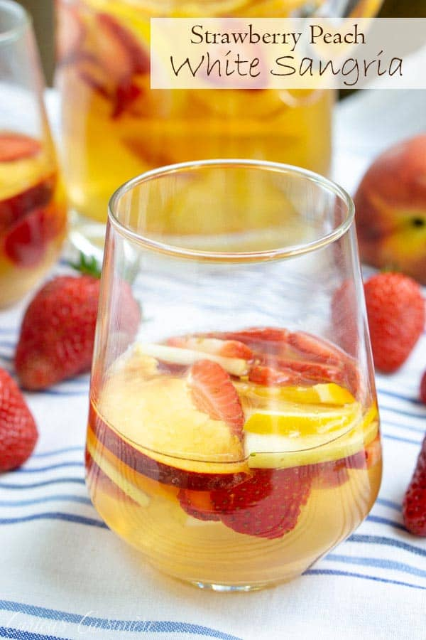 This Strawberry Peach Sangria is a fun twist on Spanish White Sangria. Fresh fruit, a crisp white wine, and a splash of brandy make this a summer favorite! #summer #drinks #wine #sangria #peaches #strawberries | www.CuriousCuisiniere.com
