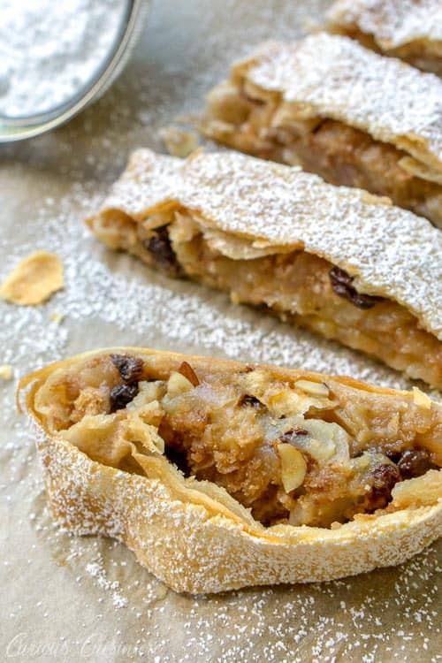 Wiener Apfelstrudel is a classic Viennese apple dessert that you probably know by the name of Apple Strudel. Flaky layers of strudel dough encase a bright fall apple filling that is studded with raisins and almonds. If you love apple pie, apple strudel is sure to be a winning recipe!| www.CuriousCuisiniere.com