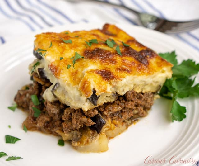 Greek Moussaka is an eggplant casserole filled with layers of eggplant and a warmly spiced meat sauce, all covered in a rich béchamel sauce. This is a recipe for some serious Greek comfort food! | www.CuriousCuisiniere.com