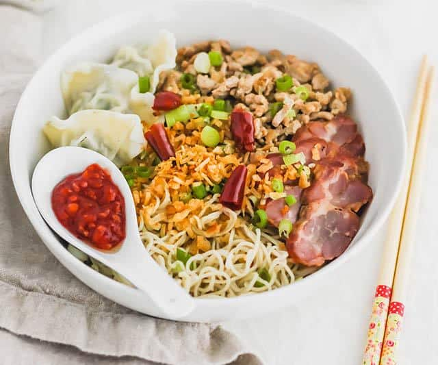Kolo Mee is a Sarawak Malaysian dish of dry noodles tossed in a savoury pork and shallot mixture, topped off with fragrant fried onions. A classic staple food in Malaysia, it is eaten for breakfast, lunch, or dinner.  | www.CuriousCuisiniere.com