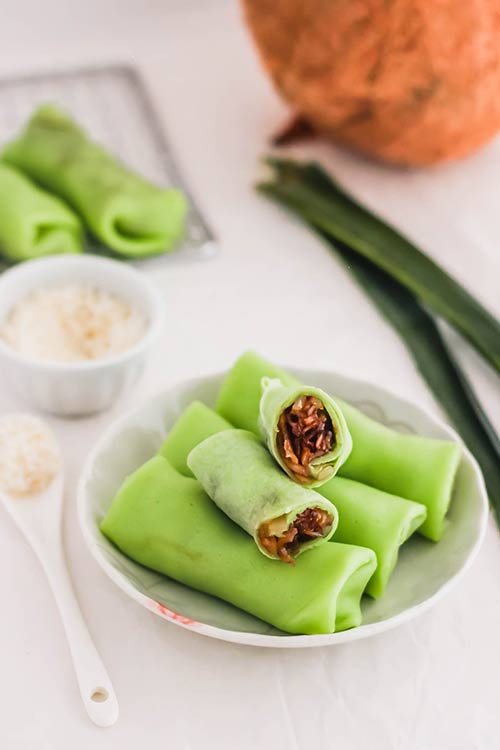 Kueh dadar is a Southeast Asian snack with a vibrant color. Image with crepe opened to see filling. | www.CuriousCuisiniere.com