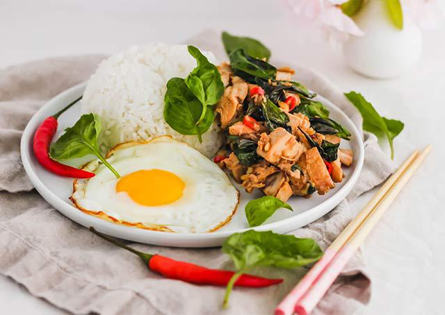 Pad Krapow Gai, Thai Basil Chicken served over rice with a fried egg. | www.CuriousCuisiniere.com