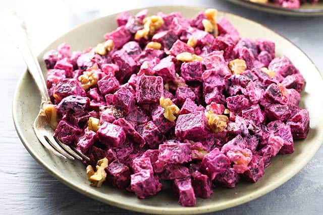 Russian Beet Salad with Prunes and Walnuts in a bowl with a fork/ | www.CuriousCuisiniere.com