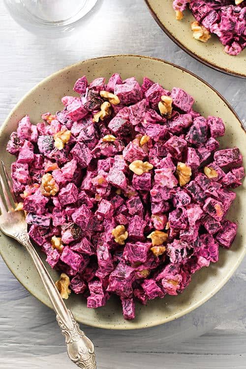Overhead image of Russian Beet Salad with Prunes and Walnuts in a bowl with a fork/ | www.CuriousCuisiniere.com