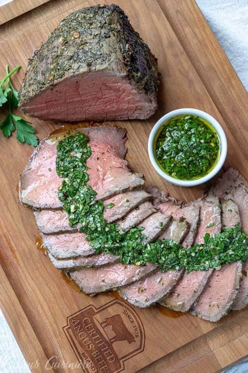 Top down view of a top round roast sliced with chimichurri sauce. | www.CuriousCuisiniere.com
