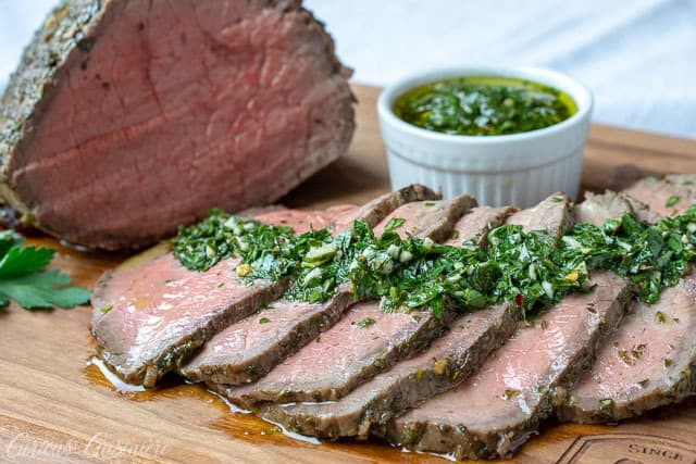 Horizontal shot of a chimichurri marinated top round beef roast. Served with a side of chimichurri.