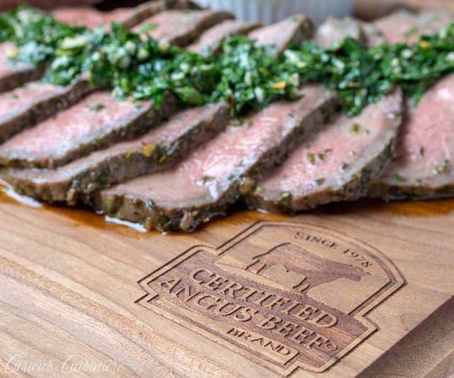 Sliced top round roast with chimichurri sauce on a Certified Angus Beef Brand branded wood cutting board.