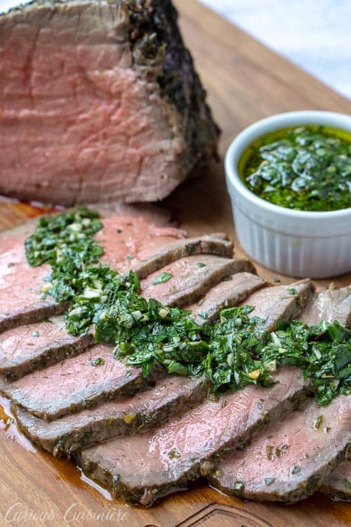 Sliced top round roast beef with chimichurri sauce. A perfect holiday roast recipe.