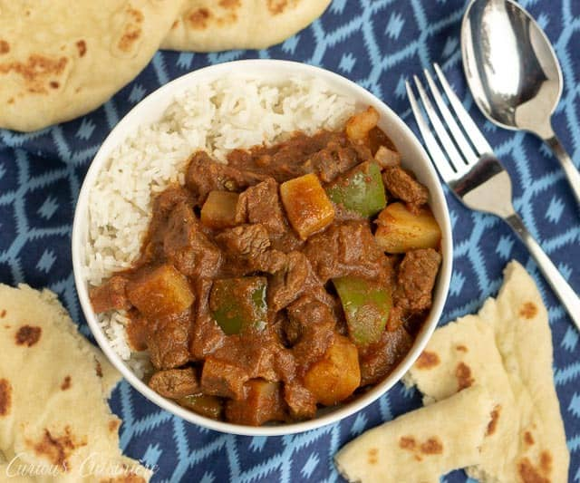 Overhead image of Beef Madras Curry with Vegetables and rice and naan flatbread. | www.CuriousCuisiniere.com