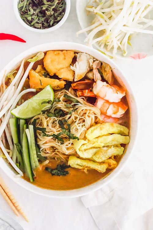 Top down of full sarawak laska bowl soup with chicken and noodles | www.CuriousCuisiniere.com