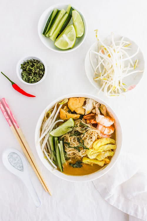 Sarawak laska bowl with garnishes of bean sporuts and cucumbers | www.CuriousCuisiniere.com