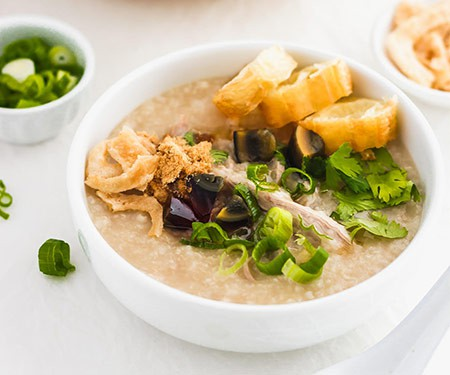 Preserved century egg congee with green onions and fried yu tiao Chinese donuts. | www.CuriousCuisiniere.com