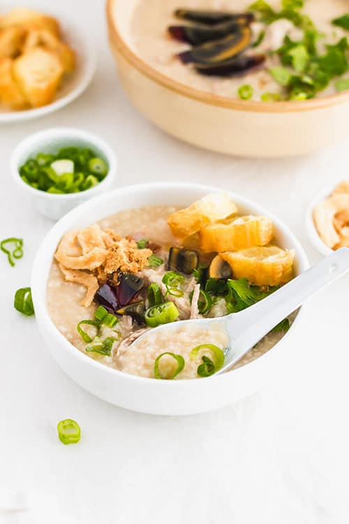 A spoon in a bowl of century egg and pork congee with green onions and fried yu tiao Chinese donuts. | www.CuriousCuisiniere.com