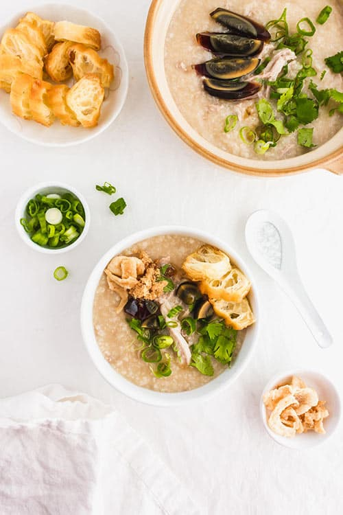 A pot and a bowl of preserved century egg congee with green onions and fried yu tiao Chinese donuts and green onions. | www.CuriousCuisiniere.com