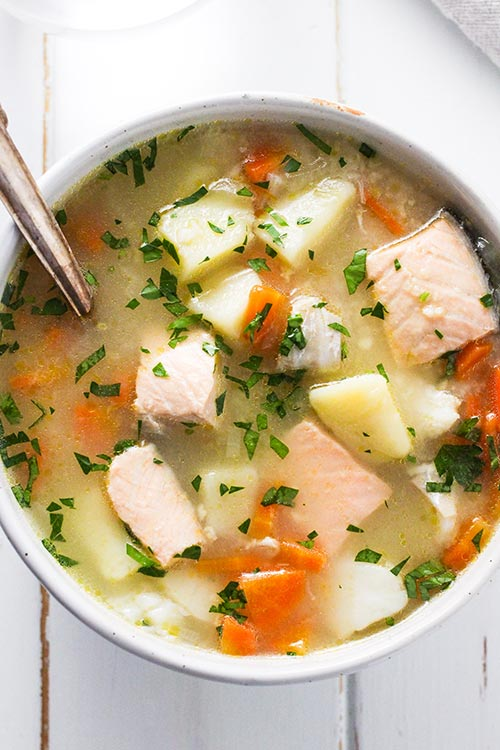 Overhead view of a bowl of Ukha, Russian fish soup. Fish is gently cooked with potatoes and carrots in a rich broth seasoned with bay and black pepper. | www.CuriousCuisiniere.com