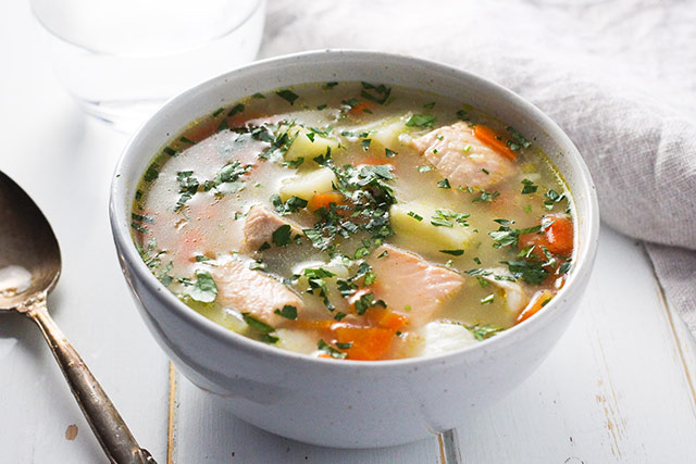 A bowl of Ukha, Russian fish soup. Fish is gently cooked with potatoes and carrots in a rich broth seasoned with bay and black pepper. | www.CuriousCuisiniere.com