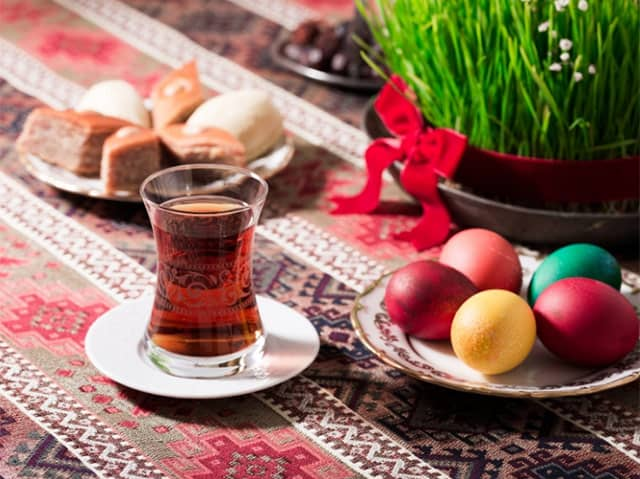 Tea, eggs, and treats for celebrating Nowruz along with a pot of sprouts.