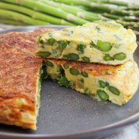 Asparagus fritatta, cut and plated with asparagus in the background.