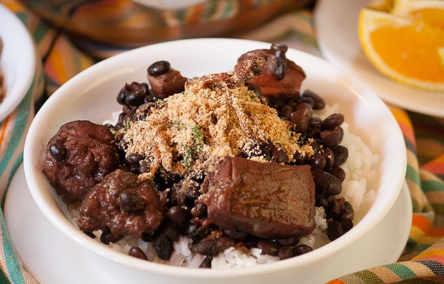 Feijoada, Brazilian black bean and pork stew with farofa, toasted cassava flour in a bowl over rice