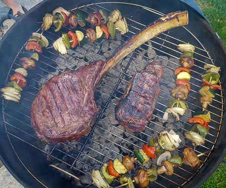 Tomahawk steak and veggie kebabs on the grill.