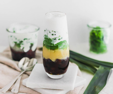 Top view of cendol, Malaysian pandan jellies, layered with red azuki beans, yellow mung beans, and coconut milk in a glass.