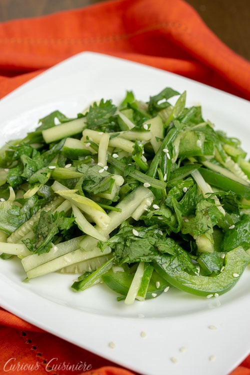 Chinese Tiger Salad - Lao Hu Cai - with cucumbers, cilantro, green peppers in a sesame oil dressing. on a white plate.