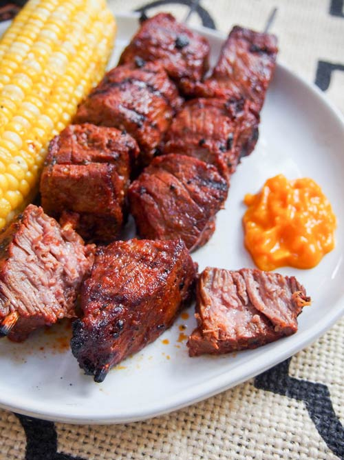 Anticuchos, Peruvian grilled beef skewers on a plate with corn and sauce, cut to show the juicy texture of the meat.