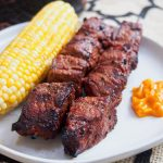 Anticuchos, Peruvian grilled beef skewers on a plate with corn