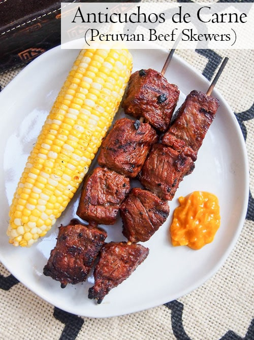 Overhead image of Anticuchos, Peruvian grilled beef skewers on a plate with corn and sauce