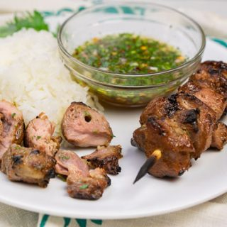 Thai pork kabobs with rice and dipping sauce with pieces taken from the skewer - cropped image