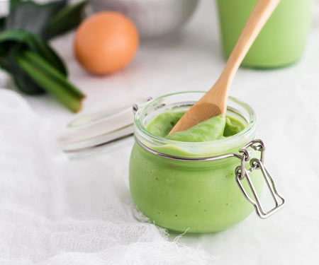 Pandan Coconut Jam in a swing top canning jar with a wooden spoon